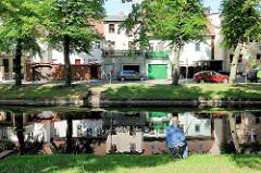 Angler mit Stohhut an der Stepenitz in Perleberg - Wohnhäuser am Fluss.