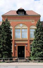 Schulgebäude, Eingang - Fassadenschmuck, Wappen von Perleberg; Inschrift DER VOLKSBILDUNG ERRICHTET. OHNE FLEISS KEINE PREIS.