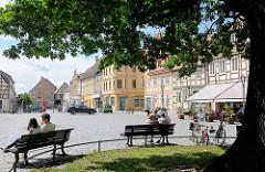 Marktplatz von Kyritz in der Sonne - Besucher der Hansestadt sitzen auf Bänken unter der Friedenseiche; 1814 zum Andenken an die Völkerschlacht von Leipzig gepflanzt.