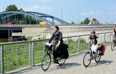 Elbrandweg in Hamburg Rothenburgsort - der Fernradwanderweg führt entlang der Elbe von Tschechien bis Cuxhaven. Fahrradweg in Hamburg Rothenburgsort am Haken - im Hintergrund die Billhorner Brückenstrasse / Strassenbrücke über den Billhafen, Oberhafe