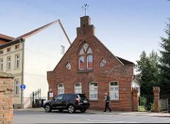 Historische Architektur in Salzwedel - Backsteingebäude, ehem. Zollhaus; Wappen der Stadt an der Fassade.