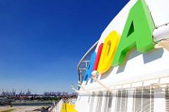 Schornstein der AIDAluna mit buntem AIDA Schriftzug - im Hintergrund Containerkräne im Hamburger Hafen.