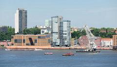 Bürohäuser am Elbufer Grosse Elbstrasse in Hamburg Altona / Altstadt; ein Schwimmkran fährt Richtung Hafen.