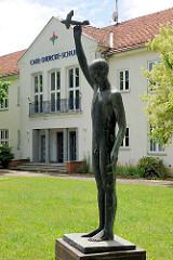 Schulgebäude Carl-Diercke-Schule in Kyritz, Pritzwalker Strasse. Bronzeskulptur - nackter Junge mit Flugzeug, Flieger.