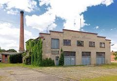 Einfache Gewerbearchitektur - schlichte Putzfassade, Garagentor - Fabrikschornstein; Architekturbilder aus Perleberg.