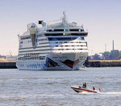 Das Kreuzfahrtschiff AIDAluna wendet im Hamburg Hafen - im Hintergrund Steinwerder; ein kleines Sportboot in Fahrt auf der Elbe.