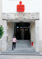 Bauschmuck am Eingang der Sparkasse in der Hansestadt Salzwedel. Reliefdekor Berufe mit Innungswappen:  Zimmermann, Tuchbreiter, Schmied, Mauerer.