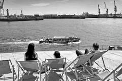 Blick von der Terrasse am Unileverhaus in der Hamburger Hafencity auf die Norderelbe; am gegenüber liegenden Elbufer Hafenkräne im Hafenstadtteil Kleiner Grasbrook. Ein Fahrgastschiff der Hafenrundfahrt Maritime Circle Line fährt Richtung Landungsbrü