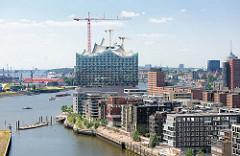 Blick über den Grasbrookhafen mit den modernen Wohnhäuser am Dalmannkai - Baukräne an der Baustelle der Elbphilharmonie.