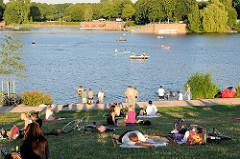 Stadtparksee in der Abendsonne - ParkbesucherInnen liegen auf der Wiese am Seeufer - Boote auf dem See; Bilder aus Hamburg Winterhude.