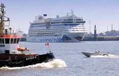 Das Kreuzfahrtschiff AIDAluna wendet im Hamburg Hafen - der Schlepper Bugsier 18 und ein Motorboot in Fahrt.