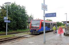 Bahnhof in Kyritz - Fahrgäste im Regen, Regionalzug am Bahnsteig.
