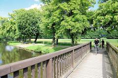 Holzbrücke über die Stepenitz, Fahrradfahrer - im Hintergrund die Hagenpromenade, Bäume - Grünanlage.