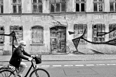 Verfallenes Wohnhaus mit vernagelten Fenstern - Fahrradfahrerin; Schwarz-Weiss Fotografie / Bilder aus Salzwedel.