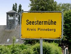 Ortsschild Seestermühe, Kreis Pinneberg - Uhrenturm Gutshaus von Kielmansegg.
