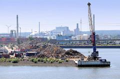 Schrotthaufen und Ladekran am Rosskai / Rosshafen im Hamburger Hafen - im Hintergrund das Kraftwerk Mooburg.