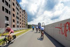 Elbrandweg in Hamburg Rothenburgsort - der Fernradwanderweg führt entlang der Elbe von Tschechien bis Cuxhaven. FahrradfahrerInnen auf dem Fahrradweg am Billehafen in Hamburg Rothenburgsort.