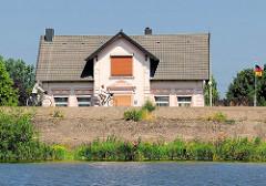 Einzelhaus, Wohnhaus hinter dem Deich - RadfahrerIn auf der Deichstrasse in Hamburg Moorfleet.