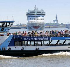 Das Kreuzfahrtschiff AIDAluna wendet im Hamburg Hafen - eine vollbesetzte Hafenfähre fährt vorüber; Aufschrift Ihr sicherer Hafen.