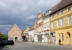 Farbige Hausfassaden historischer, restaurierter Häuser am Marktplatz von Kyritz - dunkler Regenhimmel, Wolken / Sonnenschein.