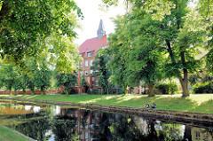 Blick über die Stepenitz in Perleberg - Schulgebäude zwischen Bäumen.