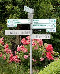 Hinweisschilder für Fahrradtouren - Ortschilder in Seestermühe; blühende Rosen am Strassenrand.