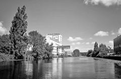 Lagerhaus mit Kranausleger am Kanalufer vom Billbrookkanal im Hamburger Stadtteil Billbrook; Bäume und Sträucher am Ufer des Kanals - Schwarz-Weiss Aufnahme.