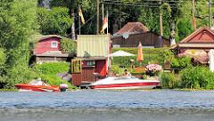 Schrebergarten - Kleingarten;  Häuser mit roter Fassade, rote Sportboote an der Bille in Hamburg Rothenburgsort.