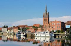 Stadthafen von Grabow an der Elde am Abend - Sportboote haben als Gastlieger an der Kaimauer angelegt - Kirchturm der St. Georg Kirche.