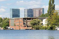 Ein altes Gewerbegebäude am Ufer der Bille in Hamburg Hammberbrook wird abgerissen - - im Hintergrund die Hochhäuser am Berliner Tor.