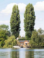 Schrebergarten, Kleingarten am Ufer der Bille in Hamburg Rothenburgsort - Sportboot am Anleger, hohe Pappeln.
