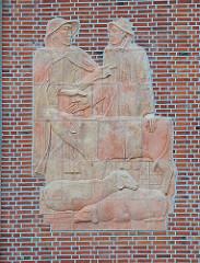 Fassadenschmuck an der Fassade der Alten Rindermarkthalle in Hamburg St. Pauli / Neuer Kamp - Skulptur Hirten mit Regenkleidung, Schafe und Kalb.