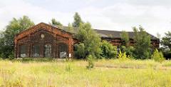 Historischer Lokschuppen am Bahnhof von Pritzwalk - historische Industrierchitektur, Ziegelgebäude mit Bäumen und Sträuchern zugewachsen.
