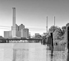 Moorfleeter Kanal in Hamburg Billbrook; rostige Dalben am Kanalufer - im Hintergrund das Kraftwerk Tiefstack mit Schornsteinen.