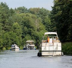 Sportboote, Motorboote zwischen Bäumen auf dem Elde Müritz Kanal.