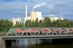 Blick über den Tiefstackkanal in Hamburg Billbrook zur Müllverbrennungsanlage / Müllverwertungsanlage MVA Borsigstrasse - ein Zug fährt über die Eisenbahnbrücke.