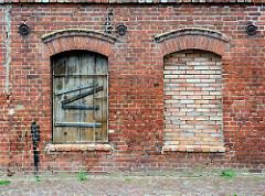 Verlassenes Backsteingebäude, Ziegelfassade - Fensteröffnungen, zugemauert + mit Holztür verschlossen - Fotos aus Grabow.