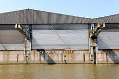 Lagerhaus mit Rollläden in Krananlage am Tidekanal in Hamburg Billbrook; Aufschrift auf der Kaimauer THYSSEN STAHLUNION.