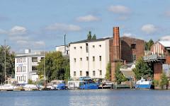 Alte Industriearchitektur am Ufer der Bille in Hamburg Hammerbrook - ein Fabrikschornstein ist teilweise abgetragen worden - Sportboote am Steg.