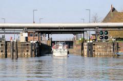 Ein Motorboot fährt vom Tiefstackkanal in die Tiefstackschleuse in Hamburg Billbrook ein - die Schleusensignale zeigen Grün an.