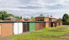 Garagen mit Holztüren - im Hintergrund Klinkerwohnhäuser, Kirchmöser, Brandenburg an der Havel.
