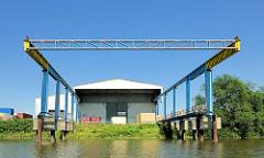 Krananlage über dem Wasser des Moorfleeter Kanals im Hamburger Stadtteil Billbrook - Lagerhalle am Ufer des Kanals.