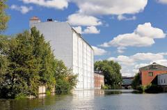 Weisse Industriearchitektur - Fabrikgebäude am Südkanal in Hamburg Hammerbrook; weisse Wolken, blauer Himmel.