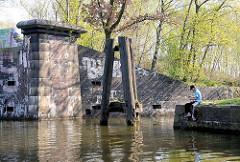 Altes Brückenfundament am Ufer des Tiefstackkanals in Hamburg Billbrook - ein Angler sitzt am Ufer.