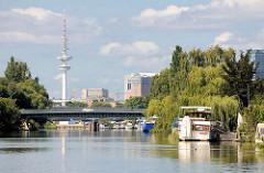 Sportboote liegen am Ufer der Schrebergärten des Bullenhuser Kanals in Hamburg Rothenburgsort - im Hintergrund die Brücke vom Ausschläger Billdeich und der Hamburger Fernsehturm.