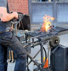 Familienfest beim Museum der Arbeit in Hamburg Barmbek Nord - Schmiede der Metallgruppe vom Museum der Arbeit führen ihre Kunst vor. Feuerstelle, Esse mit Flammen - ein Metallstab wird im Schmiedefeuer zum Glühen gebracht.