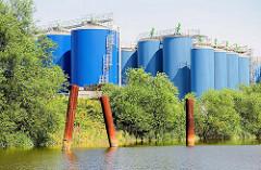 Tanklager mit blauen Tanks in Hamburg Billbrook - rostige Eisenpfähle als Anleger für Binnenschiffe / TAnker am Moorfleeter Kanal in Hamburg Billbrook.