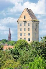 Wasserturm vom Bahnhof Pritzwalk zwischen Bäumen; das Gebäude steht unter Denkmalschutz. Im Hintergrund der Kirchturm der Pfarrkirche St. Nikolai.