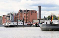 Binnenschiffe an ihren Liegeplätzen in der Billwerder Bucht in Hamburg Rothenburgsort - im Hintergrund der Wasserturm / Wasserspiele von Hamburg Rothenburgsort und die Industriearchitektur am Ausschläger Elbdeich