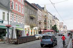 Geschäfte und Wohnhäuser in der Steinstrasse von Brandenburg a. d. Havel - Autoverkehr, Fahrradfahrer.